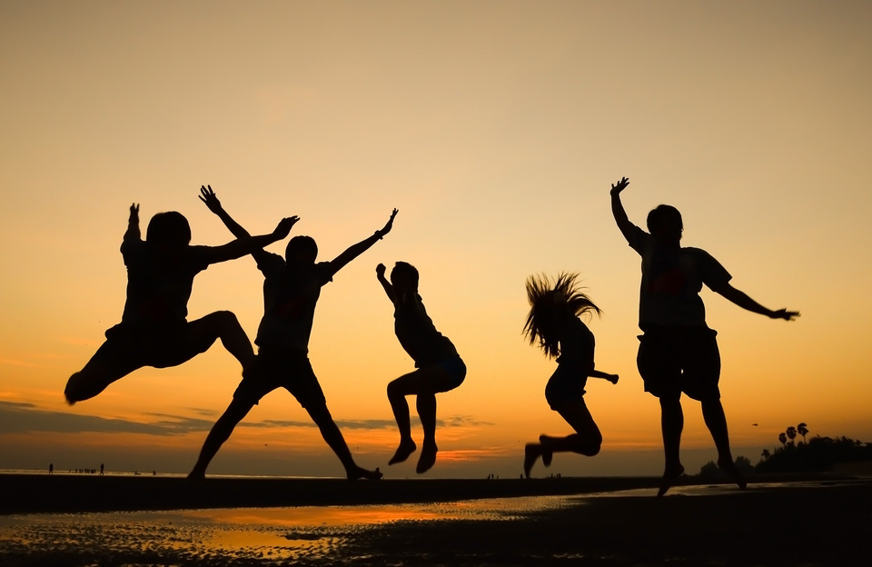 group of happy kids silhouettes jumping on the beach